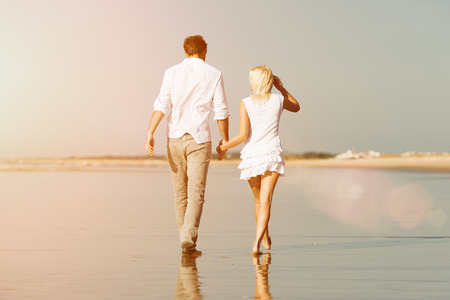 Couple on the beach in white clothing walking down, they might be on vacation or even honeymoon photo