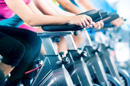 ciclismo: Grupo de cuatro personas girando en el gimnasio, ejercer sus piernas haciendo entrenamiento de cardio