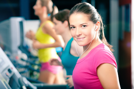 Running on treadmill in gym - group of women exercising to gain more fitness photo