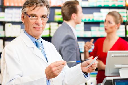 Pharmacist with customers in pharmacy, he is holding a prescription slip in his hands photo