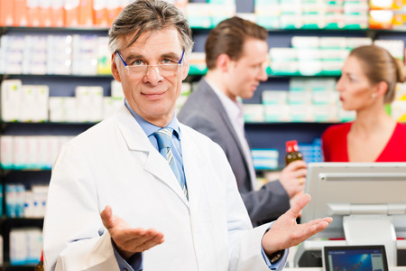 Pharmacist with customers in pharmacy, in the background are pharmaceuticals photo