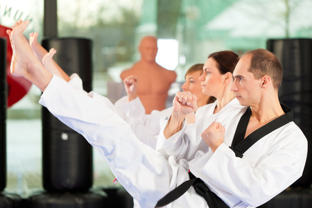martial arts woman: People in a gym in martial arts training exercising Taekwondo Stock Photo