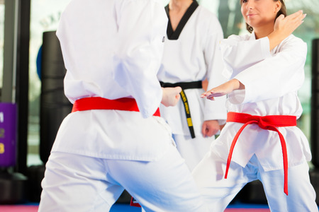fighting arts: People in a gym in martial arts training exercising Taekwondo, the trainer has a black belt Stock Photo