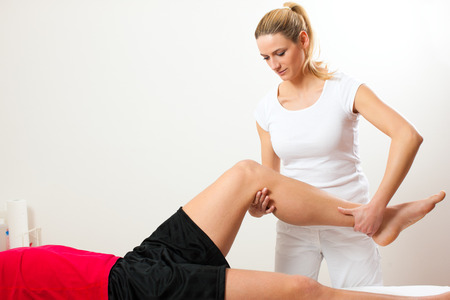 sports medicine: Patient at the physiotherapy doing physical exercises with his therapist