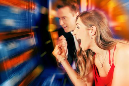 슬롯 머신 승리에 카지노 또는 놀이 아케이드 도박 커플 스톡 콘텐츠