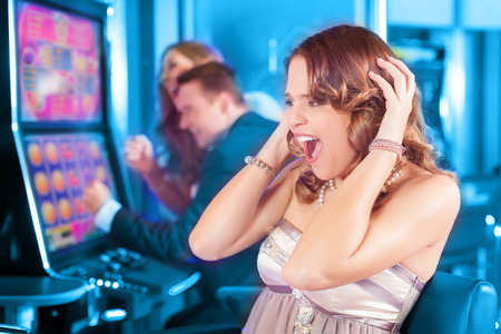 Friends gambling in Casino on slot machine, a woman is winning Stock Photo