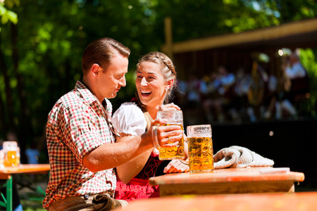 tracht: Happy Couple sitting in Beer garden and enjoy the beer and the sun Stock Photo