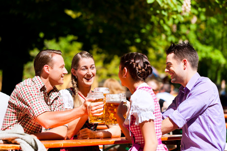 Two happy couples sitting in Bavarian Beer garden and enjoy the beer and the sun
