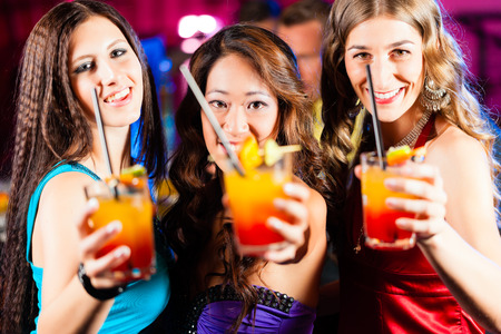 Group of party people - three female girl friends - with cocktails in a bar or club having fun photo