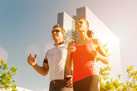 Urban sports - couple running or jogging for fitness in the city on beautiful summer day photo