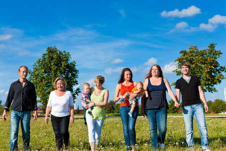 Family and multi-generation - mother, father, children and grandmother having fun on meadow in summer Stock Photo - 26489963