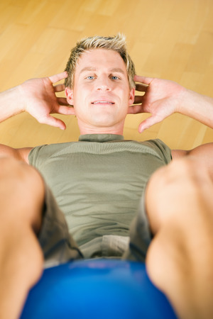 Man exercising by doing Sit-ups in a gym using a gymnastics ball photo