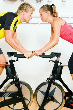 Very competitive couple bicycling in the gym against each other photo
