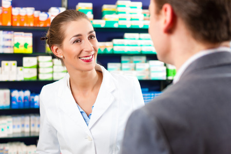 pharmacist: Female pharmacist consulting a customer in pharmacy Stock Photo