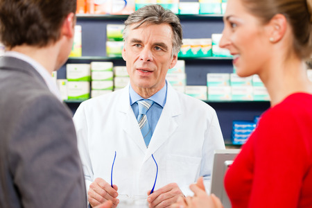 women s health: Pharmacist is consulting customers - a man and a woman - in his pharmacy