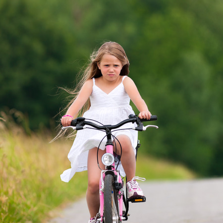 Little happy girl has a weekend excursion on her bike on a summer day in beautiful landscape photo