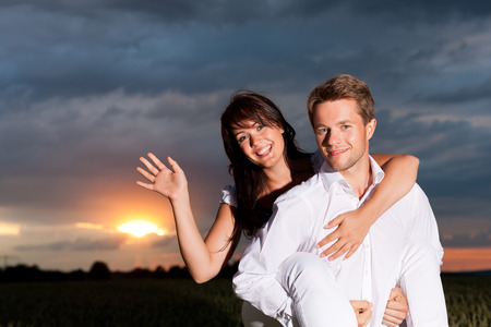 Young couple in front of cloudy sky in the evening photo