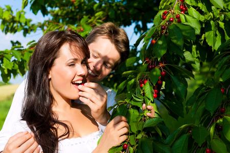 Happy couple eating cherries in summer in a garden photo