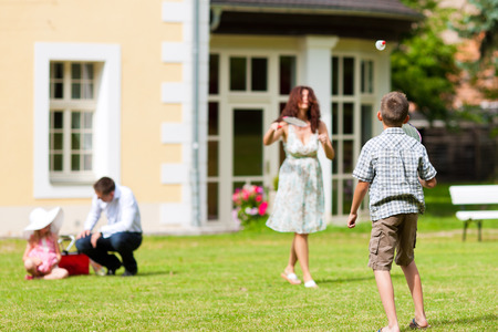 Young happy family - the children and the parents playing on the meadow photo
