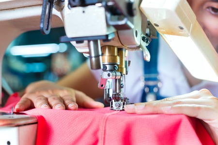 precision: Asian Seamstress or worker in an Asian textile factory sewing with a industrial sewing machine, she is very accurate Stock Photo