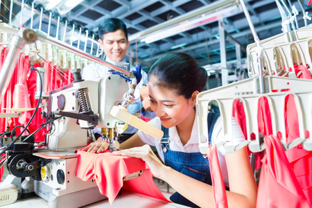 Asian Seamstress or worker in a textile factory sewing with a industrial sewing machine, she is very accurate, the manager looking pleased at her work Stock Photo