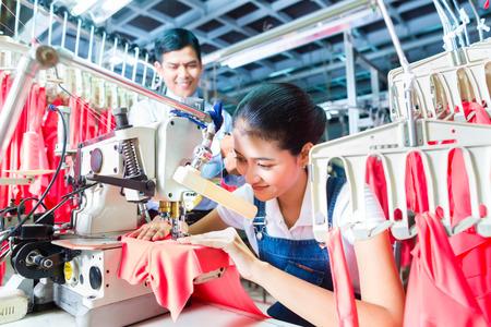 Aziatische naaister of arbeider in een textielfabriek naaien met een industriële naaimachine, ze is zeer nauwkeurig, de manager zoekt tevreden naar haar werk