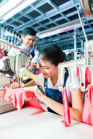 Costurera asiático o trabajador en una fábrica textil de coser con una máquina de coser industrial, que es muy preciso, el gerente busca el placer en su trabajo Foto de archivo - 26630622
