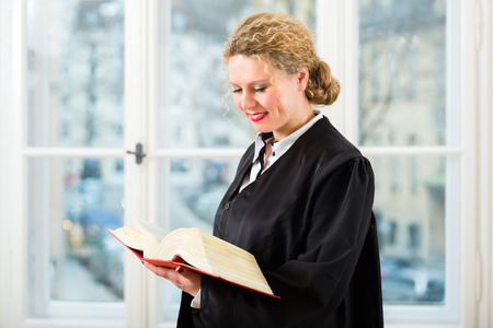 Young female lawyer working in her office reading in a typical law book photo