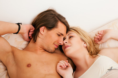Couple in bed holding each other s hand, very intimate situation, probably they had sex together chilling a bit now Stock Photo - 26611233