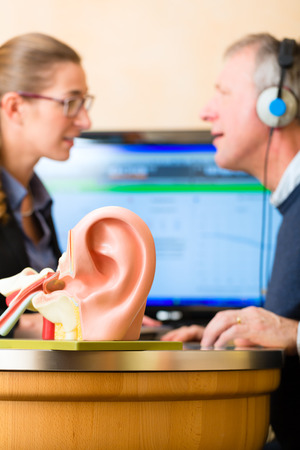 listening to people: Older man or pensioner with a hearing problem make a hearing test and may need a hearing aid, in the foreground is a model of a human ear Stock Photo