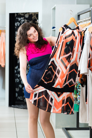 Young woman having fun while fashion shopping in boutique or store photo