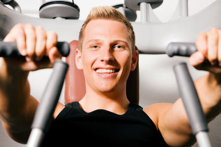 Man doing fitness training in the Gym on an exercising machine photo