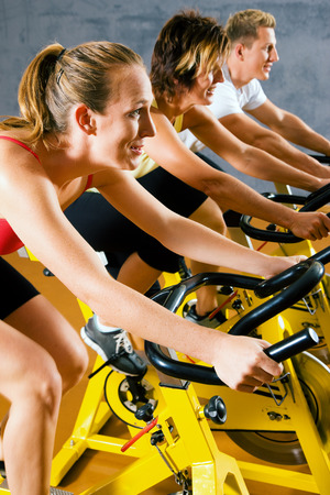 Small group of people spinning on bicycles in a gym or fitness club for a workout photo