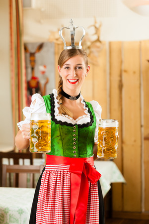 steins: Young woman as queen in Traditional Bavarian Tracht in restaurant or pub with steins and beer