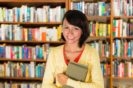Student - a young woman or girl learning in a library, she proudly holds a couple of books and smiling photo