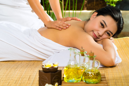 Beautiful Asian woman having a wellness back massage in a tropical setting and feeling visibly good about it Stock Photo - 26792188
