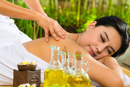Beautiful Asian woman having a wellness back massage in a tropical setting and feeling visibly good about it Stock Photo - 26792189