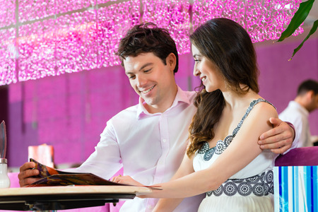 lovely couple: Young Couple in a Cafe or Ice cream parlor, looking together in the menu ordering food Stock Photo