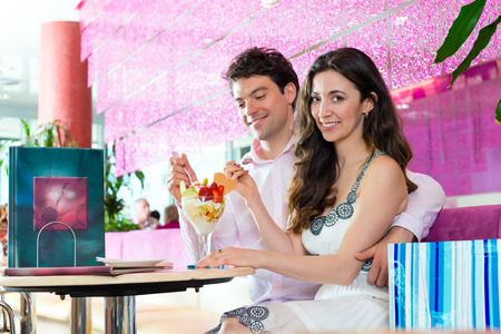 Young Couple in a Cafe eating together an ice cream sundae being happy after shopping, bags standing behind them photo