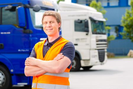 Logística - conductor orgulloso o forwarder delante de camiones y remolques, en un punto de transbordo