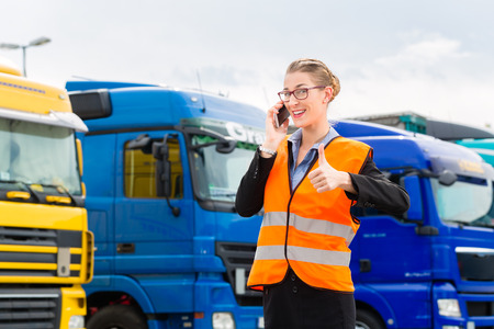 forwarder: Logistics - female forwarder or supervisor with mobile phone, in front of trucks and trailers, on transshipment point Stock Photo