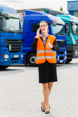 Logistics - female forwarder or supervisor with mobile phone, in front of trucks and trailers, on transshipment point photo