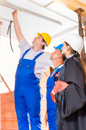 reviewer: Reviewer or expert or lawyer and builder or worker with helmets controlling a construction or building site to report defect or fault or deficiency in a protocol Stock Photo