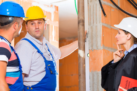 Reviewer or expert or lawyer and builder or worker with helmets controlling a construction or building site to report defect or fault or deficiency in a protocol Stock Photo