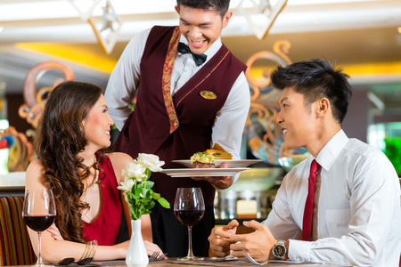 serving dish: Asian Chinese couple - Man and woman - or lovers having a date or romantic dinner in a fancy restaurant while the waiter is serving food