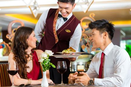 Asiatische chinesische Paare - Mann und Frau - oder Liebhaber mit einem Datum oder ein romantisches Abendessen in einem schicken Restaurant, während die Kellner die Speisen Standard-Bild