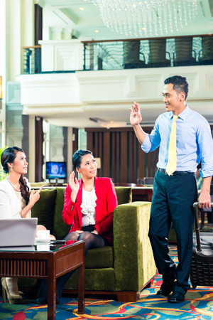 Asian Businesspeople saying goodbye in a hotel photo