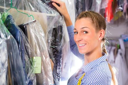 Vrouw schoner in wasserij winkel of textiel stomerijen naast kleding schoon in kledinghoezen Stockfoto