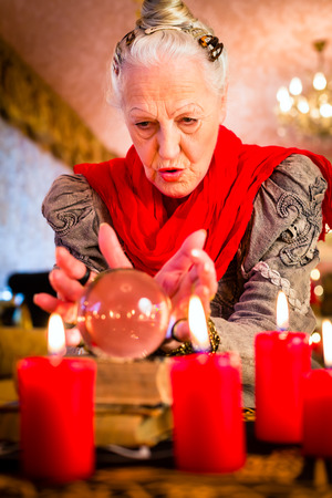 to interpret: Female Fortuneteller or esoteric Oracle, sees in the future by looking into their crystal ball during a Seance to interpret them and to answer questions Stock Photo