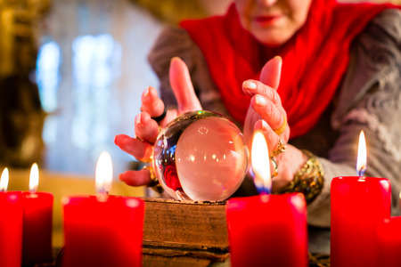 seance: Female Fortuneteller or esoteric Oracle, sees in the future by looking into their crystal ball during a Seance to interpret them and to answer questions Stock Photo